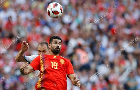Russia's Sergei Ignashevich, left, challenges for the ball with Spain's Diego Costa during the round of 16 match between Spain and Russia at the 2018 soccer World Cup at the Luzhniki Stadium in Moscow, Russia