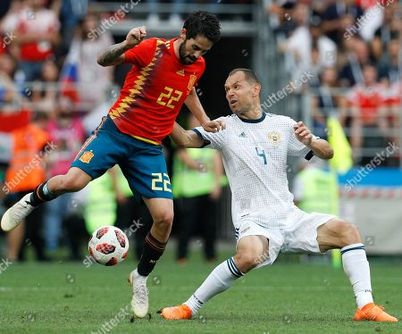 Russia's Sergei Ignashevich, right, challenges for the ball with Spain's Isco during the round of 16 match between Spain and Russia at the 2018 soccer World Cup at the Luzhniki Stadium in Moscow, Russia