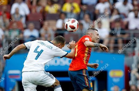 Russia's Sergei Ignashevich, left, challenges for the ball with Spain's Iago Aspas during the round of 16 match between Spain and Russia at the 2018 soccer World Cup at the Luzhniki Stadium in Moscow, Russia