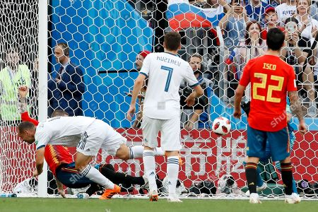 Russia's Sergei Ignashevich, left, scores an own goal during the round of 16 match against Spain at the 2018 soccer World Cup at the Luzhniki Stadium in Moscow, Russia