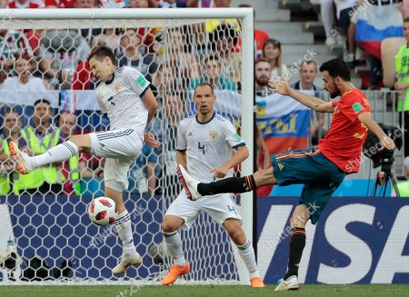 Russia's Sergei Ignashevich, center, watches Russia's Daler Kuziaev, left, trying to block a shot by Spain's Sergio Busquets, right, during the round of 16 match between Spain and Russia at the 2018 soccer World Cup at the Luzhniki Stadium in Moscow, Russia