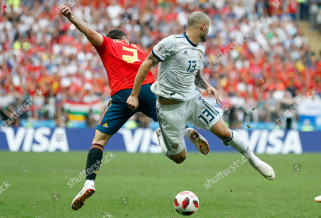 Spain's Dani Carvajal, left, and Russia's Fyodor Kudryashov challenge for the ball during the round of 16 match between Spain and Russia at the 2018 soccer World Cup at the Luzhniki Stadium in Moscow, Russia