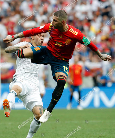 Spain's Sergio Ramos and Russia's Fyodor Kudryashov challenge during the round of 16 match between Spain and Russia at the 2018 soccer World Cup at the Luzhniki Stadium in Moscow, Russia