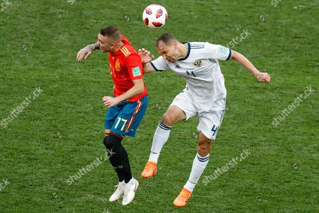 Spain's Iago Aspas, left, and Russia's Sergei Ignashevich jump the ball during the round of 16 match between Spain and Russia at the 2018 soccer World Cup at the Luzhniki Stadium in Moscow, Russia