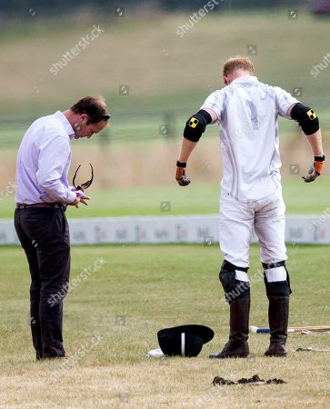 Stock Picture of Polo manager Andrew Tucker cleans glasses of Prince Harry at half time