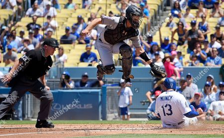 Max Muncy, Tom Murphy, Lance Barksdale. Los Angeles Dodgers' Max Muncy, right, scores on a double by Matt Kemp under the tag of Colorado Rockies catcher Tom Murphy, center, as home plate umpire Lance Barksdale, left, makes the call during the third inning of a baseball game, in Los Angeles
