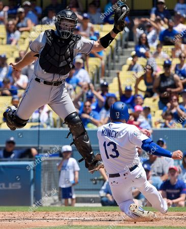 Max Muncy, Tom Murphy. Los Angeles Dodgers' Max Muncy, right, scores on a double by Matt Kemp under the tag of Colorado Rockies catcher Tom Murphy during the third inning of a baseball game, in Los Angeles