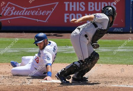 Los Angeles Dodgers' Max Muncy, left, scores on a double by Matt Kemp under the tag of Colorado Rockies catcher Tom Murphy during the third inning of a baseball game, in Los Angeles
