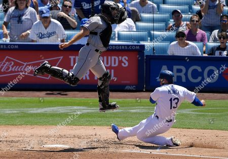 Los Angeles Dodgers' Max Muncy, right, scores on a double by Matt Kemp under the tag of Colorado Rockies catcher Tom Murphy during the third inning of a baseball game, in Los Angeles
