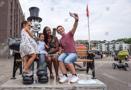 """The Neal family with Autumn-Rose aged 6 and Aurelia aged 7 months (verbal permission given for photo) pose with the """"Wallambard"""" Wallace character (after Isambard Kingdom Brunel) installed outside the SS Great Britain at Bristol Harbourside for the Gromit Unleashed 2 sculpture trail. Gromit Unleashed 2 which officially begins on 02 July will see the Academy Award®-winning character Gromit by Nick Park at Aardman Animations returning to Bristol in 2018 for the second time on sculpture trails to raise money for  the Grand Appeal charity. The character of Gromit will be joined by Wallace and their arch nemesis Feathers McGraw."""