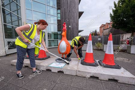 """Staff put the finishing touches to the """"Oh Bollards"""" Feathers McGraw character (disguised as a traffic cone), installed outside Aardman Animations at Bristol Harbourside for the Gromit Unleashed 2 sculpture trail. Gromit Unleashed 2 which officially begins on 02 July will see the Academy Award®-winning character Gromit by Nick Park at Aardman Animations returning to Bristol in 2018 for the second time on sculpture trails to raise money for  the Grand Appeal charity. The character of Gromit will be joined by Wallace and their arch nemesis Feathers McGraw."""