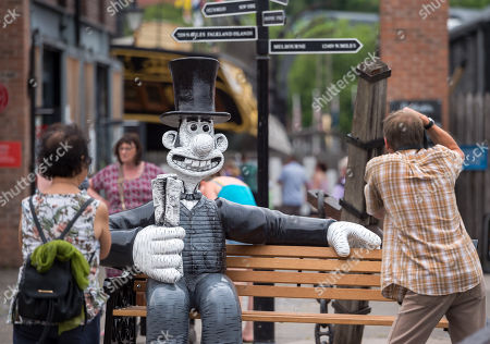 """People take pictures of the """"Wallambard"""" Wallace character (after Isambard Kingdom Brunel) installed outside the SS Great Britain at Bristol Harbourside for the Gromit Unleashed 2 sculpture trail. Gromit Unleashed 2 which officially begins on 02 July will see the Academy Award®-winning character Gromit by Nick Park at Aardman Animations returning to Bristol in 2018 for the second time on sculpture trails to raise money for  the Grand Appeal charity. The character of Gromit will be joined by Wallace and their arch nemesis Feathers McGraw."""