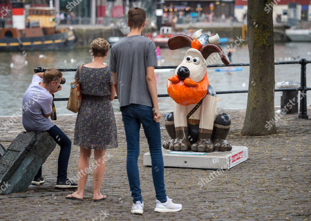 """People look at the  """"Honeydew"""" Gromit character installed at Bristol Harbourside for the Gromit Unleashed 2 sculpture trail. Gromit Unleashed 2 will see the Academy Award®-winning character Gromit by Nick Park at Aardman Animations returning to Bristol in 2018 for the second time on sculpture trails to raise money for  the Grand Appeal charity. The character of Gromit will be joined by Wallace and their arch nemesis Feathers McGraw."""