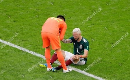 Mexico goalkeeper Alfredo Talavera, left, helps his teammate Miguel Layun at the end of the round of 16 match between Brazil and Mexico at the 2018 soccer World Cup in the Samara Arena, in Samara, Russia, . Brazil won 2-0