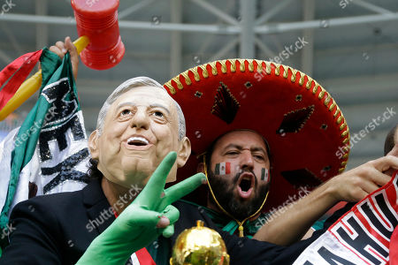 Mexican fans, one with the mask of the newly elected Mexico's President Andres Lopez Obrador, cheer prior the round of 16 match between Brazil and Mexico at the 2018 soccer World Cup in the Samara Arena, in Samara, Russia