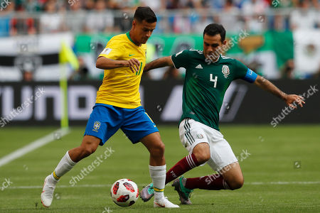 Brazil's Philippe Coutinho, left, and Mexico's Rafael Marquez challenge for the ball during the round of 16 match between Brazil and Mexico at the 2018 soccer World Cup in the Samara Arena, in Samara, Russia