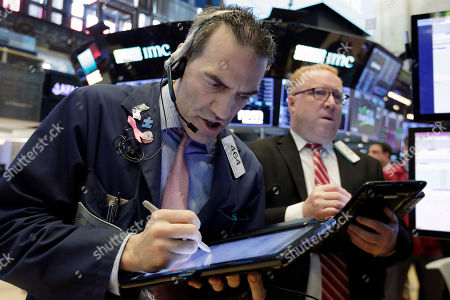 Gregory Rowe, Daniel Ryan. Traders Gregory Rowe, left, and Daniel Ryan work on the floor of the New York Stock Exchange, . U.S. stocks are falling Monday amid weak economic data from Asia and an election result in Mexico that's likely to complicate talks on renegotiating the NAFTA trade agreement