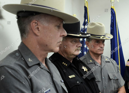 From left, Field Commander Col. Stephen Smith, Steuben County Sheriff James Allard and Troop E - Major Rick Allen listen as Gov. Andrew Cuomo talks to reporters about the death of New York State Trooper Nicholas Clark at the state police barracks in Painted Post, N.Y., . Clark, 29, was shot and killed early Monday after responding to a suicidal person barricaded inside his Erwin, N.Y., residence