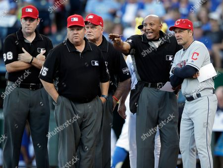 Home plate umpire CB Bucknor, second from right, talks with Cleveland Indians coach Mike Sarbaugh, right, with umpires Chris Conroy (98), Fieldin Culbreth (25) and Brian O'Nora, back, before a baseball game against the Kansas City Royals at Kauffman Stadium in Kansas City, Mo