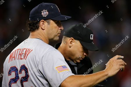 St. Louis Cardinals manager Mike Matheny (22) talks with umpire Andy Fletcher, right, during the seventh inning of a baseball game against the Arizona Diamondbacks, in Phoenix. The Cardinals defeated the Diamondbacks 6-3