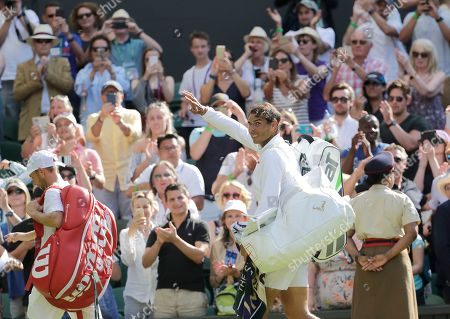 Spain's Rafael Nadal waves as he leaves the court after winning his men's singles match against Dudi Sela, left, of Israel, on the second day of the Wimbledon Tennis Championships in London