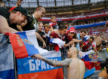 Russia's Fyodor Kudryashov, bottom, celebrates with fans after winning the round of 16 match between Spain and Russia at the 2018 soccer World Cup at the Luzhniki Stadium in Moscow, Russia, . Russia shocks Spain at the World Cup, beating the 2010 champion 4-3 in a penalty shootout after a 1-1 draw