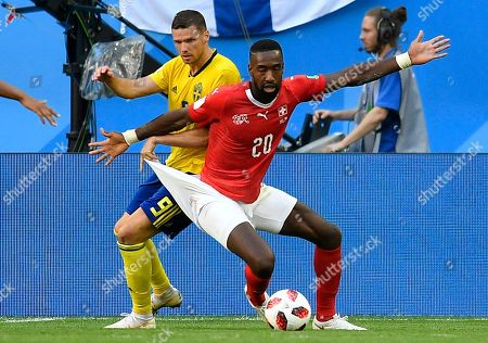 Sweden's Marcus Berg, left, and Switzerland's Johan Djourou challenge for the ball during the round of 16 match between Switzerland and Sweden at the 2018 soccer World Cup in the St. Petersburg Stadium, in St. Petersburg, Russia