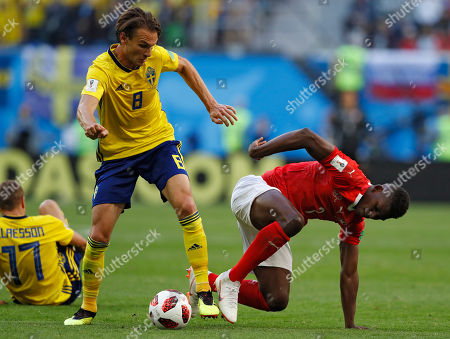 Sweden's Albin Ekdal, left, vies for the ball with Switzerland's Francois Moubandje during the round of 16 match between Switzerland and Sweden at the 2018 soccer World Cup in the St. Petersburg Stadium, in St. Petersburg, Russia
