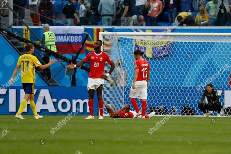 Switzerland's Johan Djourou, second left, shakes hands with Sweden's Viktor Claesson at the end of the round of 16 match between Switzerland and Sweden at the 2018 soccer World Cup in the St. Petersburg Stadium, in St. Petersburg, Russia, . Sweden won 1-0