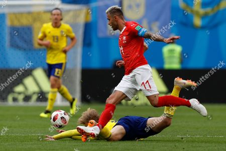 Switzerland's Valon Behrami, top, vies for the ball with Sweden's John Guidetti during the round of 16 match between Switzerland and Sweden at the 2018 soccer World Cup in the St. Petersburg Stadium, in St. Petersburg, Russia