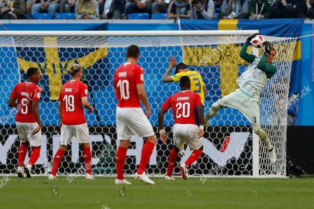 Sweden goalkeeper Robin Olsen, right, catches the ball next to Switzerland's Johan Djourou, second right, during the round of 16 match between Switzerland and Sweden at the 2018 soccer World Cup in the St. Petersburg Stadium, in St. Petersburg, Russia