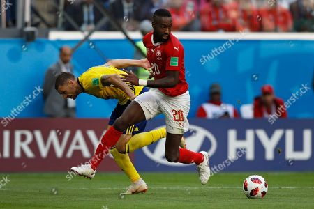 Sweden's Marcus Berg, left, battles for the ball with Switzerland's Johan Djourou during the round of 16 match between Switzerland and Sweden at the 2018 soccer World Cup in the St. Petersburg Stadium, in St. Petersburg, Russia