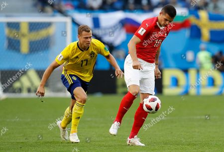Granit Xhaka, John Guidetti. Switzerland's Granit Xhaka, right, vies for the ball with Sweden's John Guidetti during the round of 16 match between Switzerland and Sweden at the 2018 soccer World Cup in the St. Petersburg Stadium, in St. Petersburg, Russia