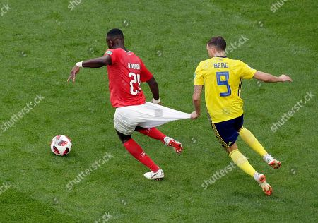 Switzerland's Johan Djourou, left, duels for the ball with Sweden's Marcus Berg during the round of 16 match between Switzerland and Sweden at the 2018 soccer World Cup in the St. Petersburg Stadium, in St. Petersburg, Russia