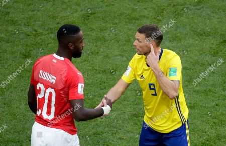 Sweden's Marcus Berg, right, discusses with Switzerland's Johan Djourou during the round of 16 match between Switzerland and Sweden at the 2018 soccer World Cup in the St. Petersburg Stadium, in St. Petersburg, Russia