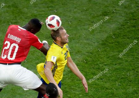 Switzerland's Johan Djourou, left, jumps for the ball with Sweden's Ola Toivonen during the round of 16 match between Switzerland and Sweden at the 2018 soccer World Cup in the St. Petersburg Stadium, in St. Petersburg, Russia