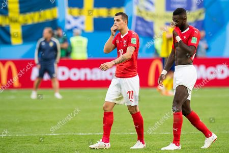 Switzerland's Granit Xhaka (L) and Johan Djourou after the FIFA World Cup 2018 round of 16 soccer match between Sweden and Switzerland in St.Petersburg, Russia, 03 July 2018. Sweden won 1-0.  (RESTRICTIONS APPLY: Editorial Use Only, not used in association with any commercial entity - Images must not be used in any form of alert service or push service of any kind including via mobile alert services, downloads to mobile devices or MMS messaging - Images must appear as still images and must not emulate match action video footage - No alteration is made to, and no text or image is superimposed over, any published image which: (a) intentionally obscures or removes a sponsor identification image; or (b) adds or overlays the commercial identification of any third party which is not officially associated with the FIFA World Cup)