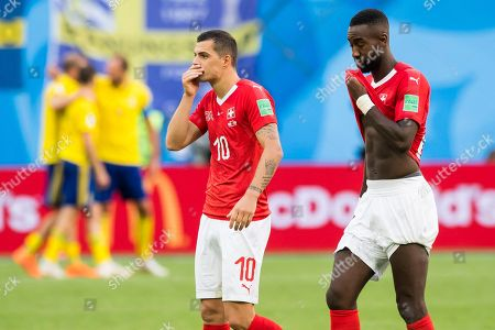 Switzerland's midfielder Granit Xhaka (L) and Switzerland's defender Johan Djourou (R) react after the  FIFA World Cup 2018 round of 16 soccer match between Sweden and Switzerland in St.Petersburg, Russia, 03 July 2018. (RESTRICTIONS APPLY: Editorial Use Only, not used in association with any commercial entity - Images must not be used in any form of alert service or push service of any kind including via mobile alert services, downloads to mobile devices or MMS messaging - Images must appear as still images and must not emulate match action video footage - No alteration is made to, and no text or image is superimposed over, any published image which: (a) intentionally obscures or removes a sponsor identification image; or (b) adds or overlays the commercial identification of any third party which is not officially associated with the FIFA World Cup)