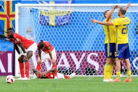 (L-R) Switzerland's defender Johan Djourou, Switzerland's defender Ricardo Rodriguez and Switzerland's defender Manuel Akanji look disappointed after loosing the FIFA World Cup 2018 round of 16 soccer match between Sweden and Switzerland in St.Petersburg, Russia, 03 July 2018. (RESTRICTIONS APPLY: Editorial Use Only, not used in association with any commercial entity - Images must not be used in any form of alert service or push service of any kind including via mobile alert services, downloads to mobile devices or MMS messaging - Images must appear as still images and must not emulate match action video footage - No alteration is made to, and no text or image is superimposed over, any published image which: (a) intentionally obscures or removes a sponsor identification image; or (b) adds or overlays the commercial identification of any third party which is not officially associated with the FIFA World Cup)