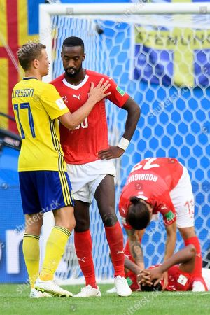 Sweden's midfielder Viktor Claesson (L) comforts (L-R) Switzerland's defender Johan Djourou, Switzerland's defender Ricardo Rodriguez and Switzerland's defender Manuel Akanji after loosing the FIFA World Cup 2018 round of 16 soccer match between Sweden and Switzerland in St.Petersburg, Russia, 03 July 2018. (RESTRICTIONS APPLY: Editorial Use Only, not used in association with any commercial entity - Images must not be used in any form of alert service or push service of any kind including via mobile alert services, downloads to mobile devices or MMS messaging - Images must appear as still images and must not emulate match action video footage - No alteration is made to, and no text or image is superimposed over, any published image which: (a) intentionally obscures or removes a sponsor identification image; or (b) adds or overlays the commercial identification of any third party which is not officially associated with the FIFA World Cup)
