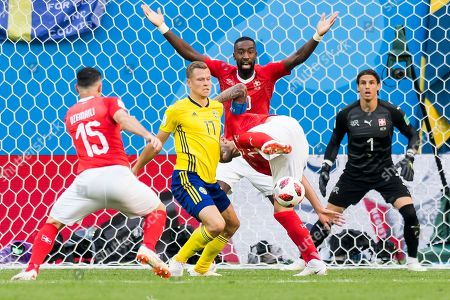 (L-R) Switzerland's midfielder Blerim Dzemaili, Sweden's midfielder Viktor Claesson, Switzerland's defender Johan Djourou, Switzerland's midfielder Valon Behrami, and Switzerland's goalkeeper Yann Sommer, fight for the ball during the FIFA World Cup 2018 round of 16 soccer match between Sweden and Switzerland in St.Petersburg, Russia, 03 July 2018. (RESTRICTIONS APPLY: Editorial Use Only, not used in association with any commercial entity - Images must not be used in any form of alert service or push service of any kind including via mobile alert services, downloads to mobile devices or MMS messaging - Images must appear as still images and must not emulate match action video footage - No alteration is made to, and no text or image is superimposed over, any published image which: (a) intentionally obscures or removes a sponsor identification image; or (b) adds or overlays the commercial identification of any third party which is not officially associated with the FIFA World Cup)