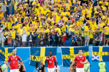 Switzerland's soccer players (L-R) Valon Behrami, Johan Djourou, and Granit Xhaka react during the FIFA World Cup 2018 round of 16 soccer match between Sweden and Switzerland in St.Petersburg, Russia, 03 July 2018. (RESTRICTIONS APPLY: Editorial Use Only, not used in association with any commercial entity - Images must not be used in any form of alert service or push service of any kind including via mobile alert services, downloads to mobile devices or MMS messaging - Images must appear as still images and must not emulate match action video footage - No alteration is made to, and no text or image is superimposed over, any published image which: (a) intentionally obscures or removes a sponsor identification image; or (b) adds or overlays the commercial identification of any third party which is not officially associated with the FIFA World Cup)
