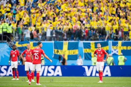 Switzerland's soccer players (from left)  Johan Djourou, Valon Behrami, Blerim Dzemaili, and Granit Xhaka react after going 0-1 down during the FIFA World Cup 2018 round of 16 soccer match between Sweden and Switzerland at the Krestovski Stadium, in St. Petersburg, Russia, Tuesday, July 3, 2018.  (RESTRICTIONS APPLY: Editorial Use Only, not used in association with any commercial entity - Images must not be used in any form of alert service or push service of any kind including via mobile alert services, downloads to mobile devices or MMS messaging - Images must appear as still images and must not emulate match action video footage - No alteration is made to, and no text or image is superimposed over, any published image which: (a) intentionally obscures or removes a sponsor identification image; or (b) adds or overlays the commercial identification of any third party which is not officially associated with the FIFA World Cup)