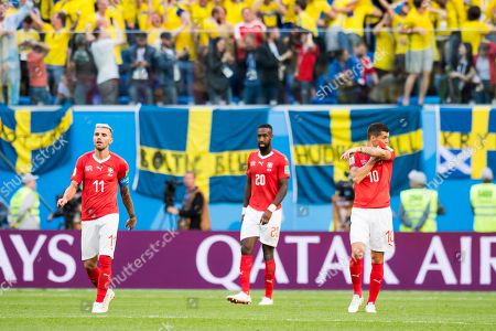 Switzerland's soccer players (from left) Valon Behrami, Johan Djourou, and Granit Xhaka react after going 0-1 down during the FIFA World Cup 2018 round of 16 soccer match between Sweden and Switzerland at the Krestovski Stadium, in St. Petersburg, Russia, Tuesday, July 3, 2018.  (RESTRICTIONS APPLY: Editorial Use Only, not used in association with any commercial entity - Images must not be used in any form of alert service or push service of any kind including via mobile alert services, downloads to mobile devices or MMS messaging - Images must appear as still images and must not emulate match action video footage - No alteration is made to, and no text or image is superimposed over, any published image which: (a) intentionally obscures or removes a sponsor identification image; or (b) adds or overlays the commercial identification of any third party which is not officially associated with the FIFA World Cup)
