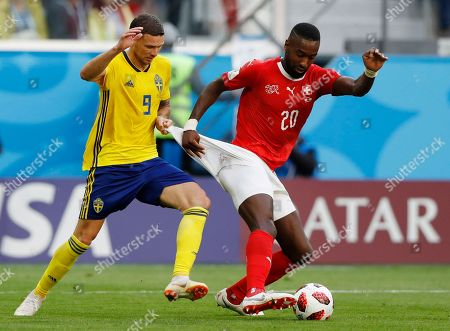 Stock Picture of Sweden's Marcus Berg, left, battles for the ball with Switzerland's Johan Djourou during the round of 16 match between Switzerland and Sweden at the 2018 soccer World Cup in the St. Petersburg Stadium, in St. Petersburg, Russia
