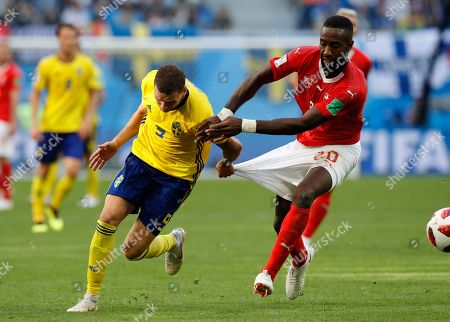 Switzerland's Johan Djourou, right, duels for the ball with Sweden's Marcus Berg during the round of 16 match between Switzerland and Sweden at the 2018 soccer World Cup in the St. Petersburg Stadium, in St. Petersburg, Russia