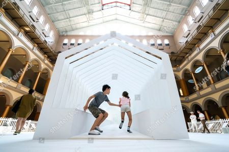 Visitors Ben Smith (C-L) and Sarah Smith (C-R) play in the exhibit Fun House, the latest of the 'Summer Block Party' installations at the National Building Museum in Washington, DC, USA, 03 July 2018. The heart of the exhibit, which officially opens 04 July, is a freestanding structure that 'recalls and re-imagines the idea of the traditional home.'