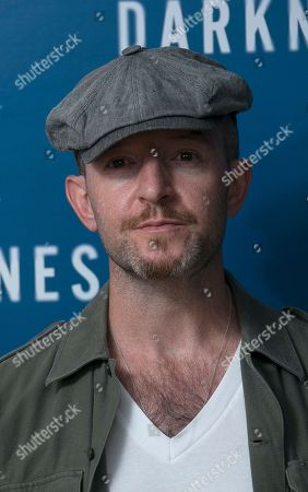 Anthony Byrne poses for photographers upon arrival at the screening of In Darkness in central London
