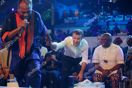 French President Emmanuel Macron, center, is invited on the stage by Femi Kuti, son of late Afrobeat legend Fela Anikulapo Kuti, during an event to celebrate African Culture at the New Afrika shrine in Lagos, Nigeria, . Macron arrived Abuja earlier for a meeting with his Nigerian counterpart Muhammadu Buhari, in his latest attempt to forge closer ties with English-speaking Africa