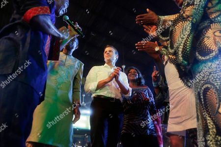 French President Emmanuel Macron, center, dances with Femi Kuti, son of late Afrobeat legend Fela Anikulapo Kuti, during an event to celebrate African Culture at the New Afrika shrine in Lagos, Nigeria, . Macron arrived in Abuja earlier for a meeting with his Nigerian counterpart Muhammadu Buhari, in his latest attempt to forge closer ties with English-speaking Africa